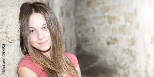 portrait of cute teenager girl beauty against ancient old wall rocks outdoor