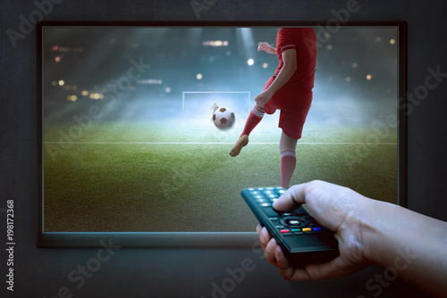Fototapeta People hands with remote watching football game