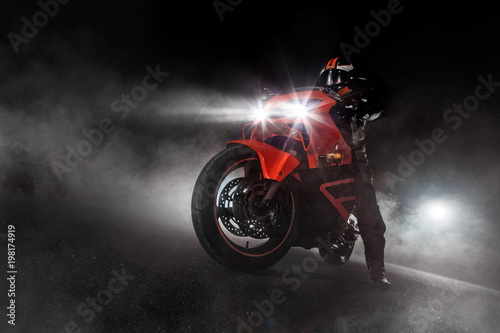 Supersport motorcycle driver at night with smoke around - 198174919