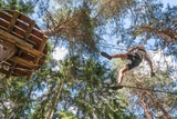 Teenager having fun on high ropes course, adventure, park, climbing trees in a forest in summer - 198178766