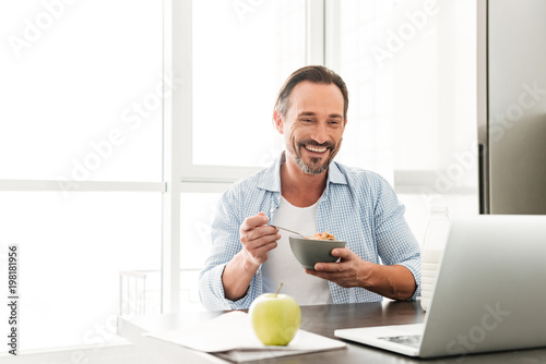 Uśmiechnięty dorośleć mężczyzna ma zdrowego śniadanie