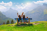 family sitting on a bench in nature and looking at the view of a mountain landscape, the sky and beautiful panorama