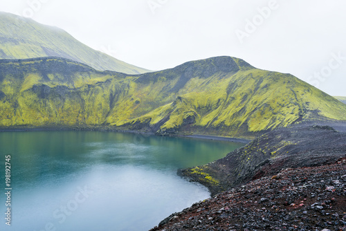 Fotobehang Pistache Kratersee mit blauem Wasser und grünen Bergen
