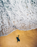 Breath taking drone shot of surfer on a beach on a sunny day