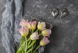on a gray background in a pink plate there are pink tulips, gray pearls and two retro hearts