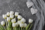 on a gray background lie white tulips, pearls and two white hearts