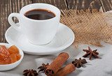 Food - a cup of hot aromatic coffee and spices on an old wooden background.