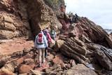 hikers walking on the rocks near the sea