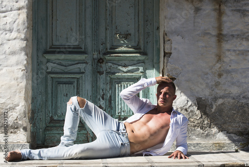 Man with nude torso lies outdoor, suntanning. Sexy macho relaxing under sunlight with ancient rocky wall and old door on background. Guy enjoys sunny day. Sexy and erotic concept. - 198229372