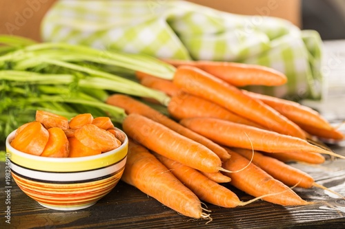 Whole carrots and a bowl of sliced