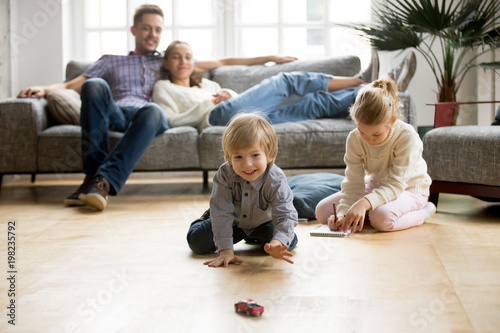 Leinwandbild Motiv Cute kids playing while parents relaxing sofa at home together, smiling active boy entertaining with toy car near his sister on floor, happy family spending time together in living room on weekend