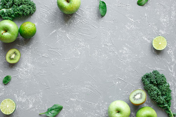 Fresh green fruits, kale and spinach on gray background with copy space, top view