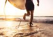 Leinwandbild Motiv Man surfer run in ocean with surfboard. Active vacation, health lifestyle and sport concept image