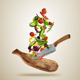 Flying pieces of vegetable with cutting board and knife