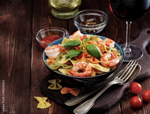 Fototapeta Delicious farfalle pasta with shrimps on wooden background. Mediterranean cuisine
