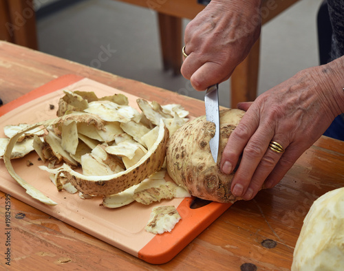 older female hands cut celery with a kitchen knife on a wooden table, preparation for cooking