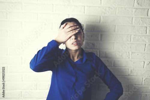 handsome businesswoman having head on  brick wall background