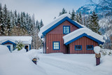 View of traditional wooden houses covered with snow in stunning nature background in Norway