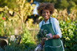 african american woman holding freshly picked kale from comnunal community garden posing for portrait
