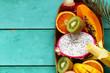 fresh tropical fruits - rambutan, papaya, kiwi, mango on a wooden background