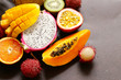 fresh tropical fruits - rambutan, papaya, kiwi, mango on a wooden background