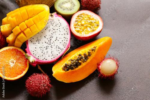 świeże owoce tropikalne - rambutan, papaja, kiwi, mango na drewnianym tle