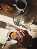 Two couple hands hold a coffee and water, date in cafe