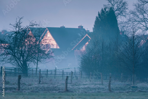 Fotobehang Blauwe jeans Houses in misty countryside lit by morning sunlight.