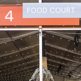 Food court - a large sign above the canopy of a place to feed on open air. Summer entertainment, festival