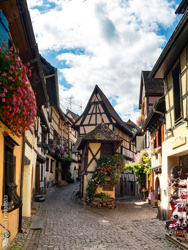 Beautiful view of the historic town square of Eguisheim, a popular tourist destination along the famous Alsace Wine Route, on a sunny day with blue sky, Alsace, France © ikmerc