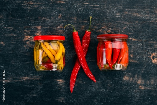 Plexiglas Hot chili peppers Pickled hot peppers chili. On a black wooden background. Top view. Copy space for your text.
