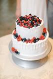 White wedding cake decorated with fresh berries