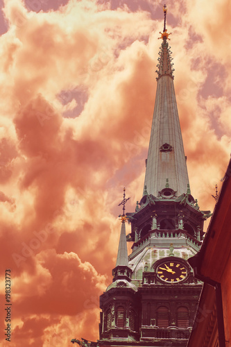 Fotobehang Stockholm Spire of German Church located in Old Town (Gamla Stan) of Stockholm, Sweden agaisn a drama red sky (toned)