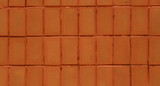 Wall of red tiles close-up. Abstract background. Geometric pattern