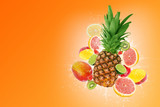 Fresh fruits, pineapple surrounded with grapefruit, lime, kiwi, mango, strawberries in water splash, isolated on orange background with free space