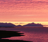Incredibly beautiful dawn (sunset) on the shore of the Atlantic Ocean. Silhouettes of mountains and red clouds. Iceland.