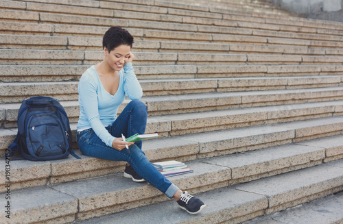 Pretty shorthaired woman sitting on the steps looking in notebook outdoors