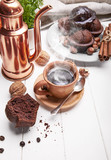 Coffee in clay cup with chocolate muffin on white wooden board