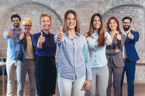 Group of happy business people and company staff in modern office, representig company, showing thumbs up.