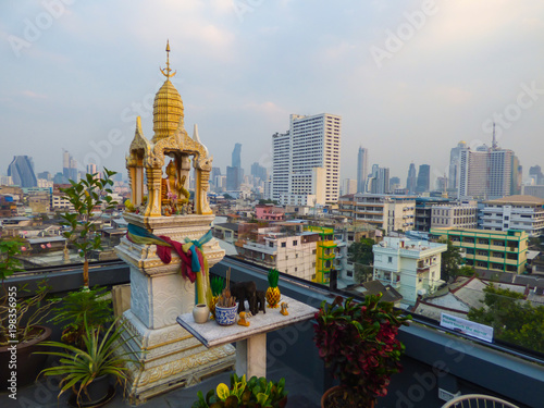 Fotobehang Bangkok Spirit house and Bangkok's skyline in the background - view from a rooftop bar