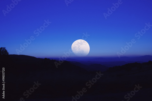 Fotobehang Donkerblauw Full Moon from the mountain silhouettes landscape.