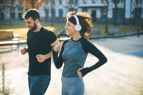 Fototapeta Healthy runners running in city cityscape background