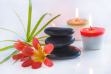 Beautiful spa compostion with black massage stones, red flowers and burning candles on white glossy background - 198373314