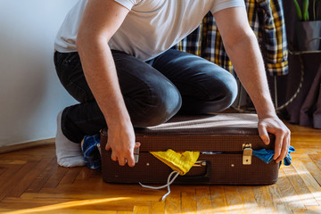 man need help to close suitcase. overloaded bag with clothes. travel concept