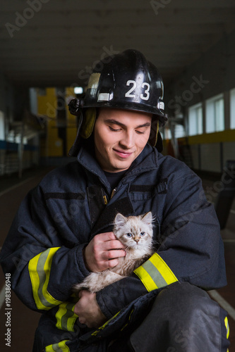 firefighter plays with a kitten, hugs, rejoices