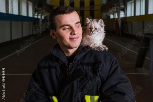 strażak gra z kotkiem, ściska, raduje się