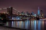 Purple sunset view of Brooklyn bridge and lower Manhattan skyline