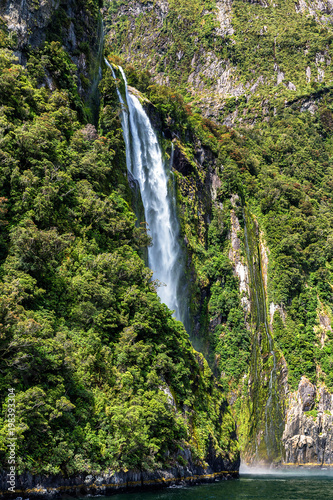 High waterfall in Milford Sound, picture taken from cruise ferry. - 198393304