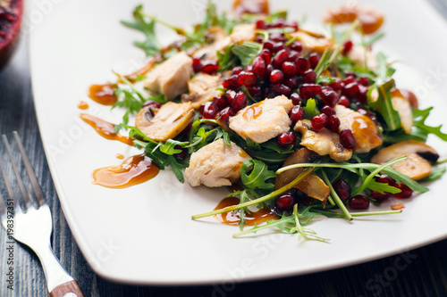 Appetizing chicken salad with pomegranate seeds and arugula on white plate, restaurant serving. Healthy and tasty food