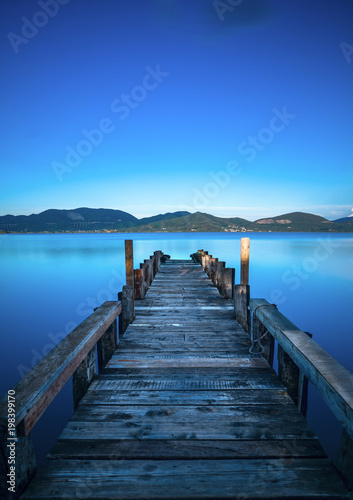 Plexiglas Pier Wooden pier or jetty on a blue lake sunset and sky reflection on water. Versilia Tuscany, Italy